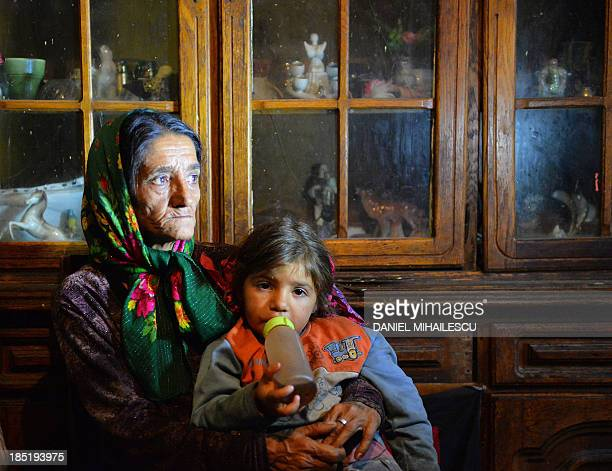 A Roma woman holds her grandaughter inside her home at Roma neighborhood in Tinca village on October 17 2013 A centre for Roma people built by the...