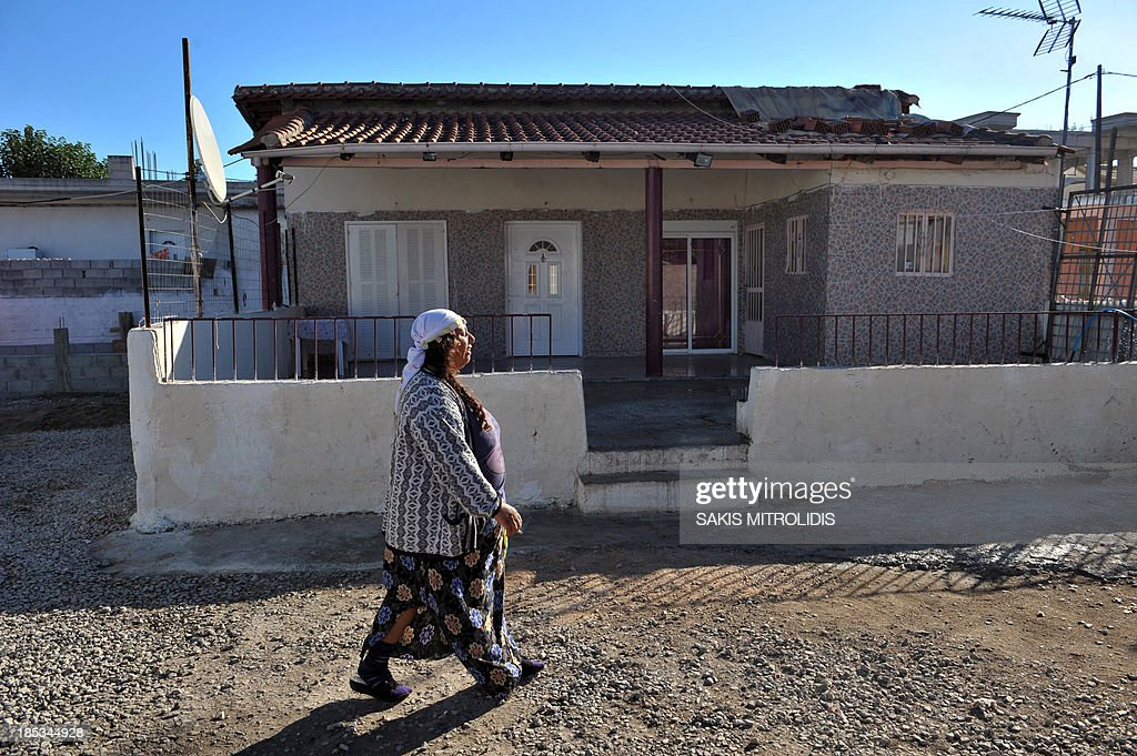 A Roma woman walks next to the house where a 4-year-old blonde girl lived in Farsala, central Greece, on 19 October, 2013. Yesterday Greek police released a handout photo showing Maria, a 4-year-old blonde girl who was found on October 17, 2013 near Farsala during a nationwide crackdown on illegal activities by Roma. An appeal was launched by Greek authorities to help identify the girl who was allegedly snatched from her parents by a couple with whom she was found living in a Roma settlement. AFP PHOTO /Sakis Mitrolidis