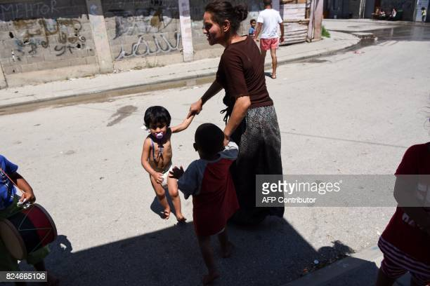 A Roma woman walks with her children in the Roma neighborhood in the town of Mitrovica on July 7 2017 The Roma 'are not treated like humans' Florim...