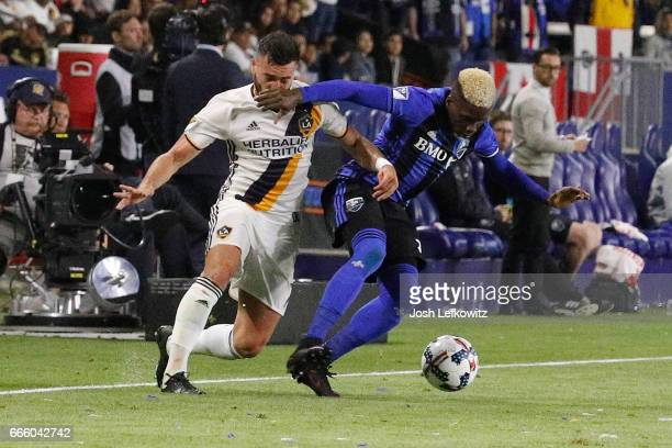 Romain Alessandrini of Los Angeles Galaxy and Ambroise Oyongo of Montreal Impact fight for possesion of the ball during Los Angeles Galaxy's MLS...
