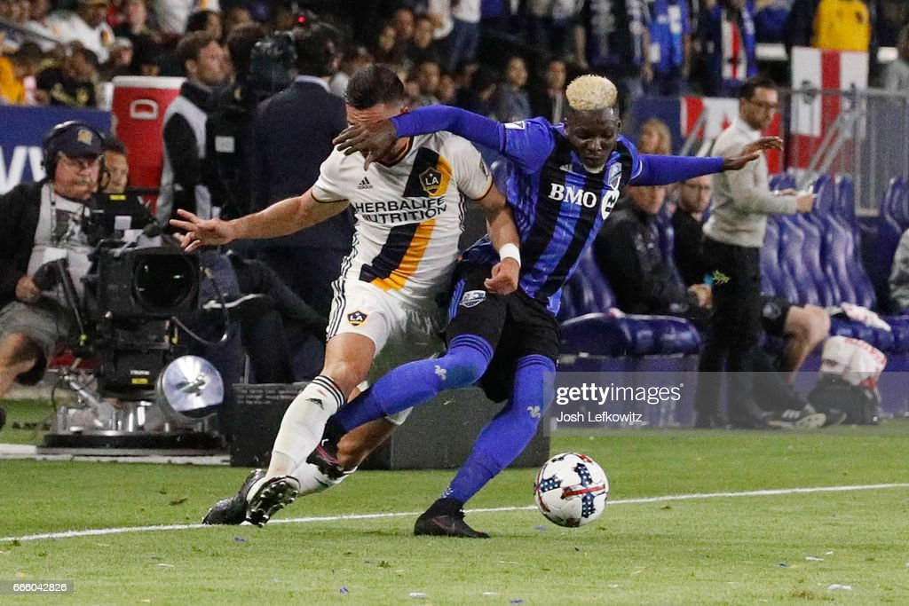 Romain Alessandrini #7 of Los Angeles Galaxy and Ambroise Oyongo #2 of Montreal Impact fight for possesion of the ball during Los Angeles Galaxy's MLS match against Montreal Impact at the StubHub Center on April 7, 2017 in Carson, California.