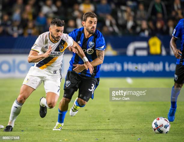 Romain Alessandrini of Los Angeles Galaxy charges as Hernan Bernardello of Montreal Impact defends during Los Angeles Galaxy's MLS match against...