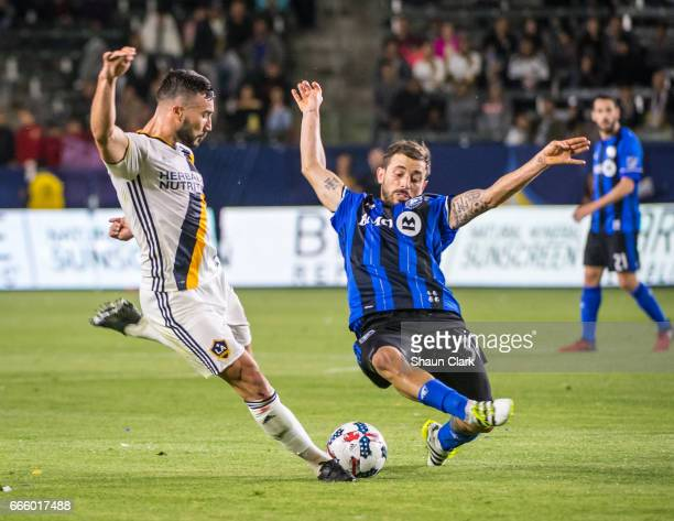 Romain Alessandrini of Los Angeles Galaxy takes a shot as Hernan Bernardello of Montreal Impact defends during Los Angeles Galaxy's MLS match against...