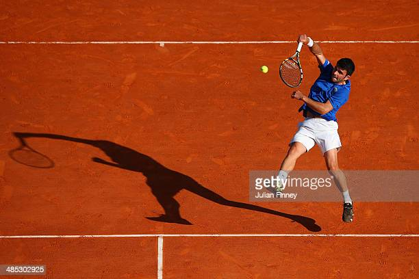 Romain Arneodo plays a smash with partner Benjamin Balleret of Monaco in their doubles match against Andreas Seppi of Italy and Roberto Bautista Agut...