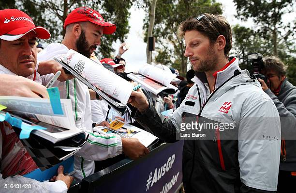 Romain Grosjean of France and Haas F1 arrives at the circuit and signs autographs for fans during qualifying for the Australian Formula One Grand...