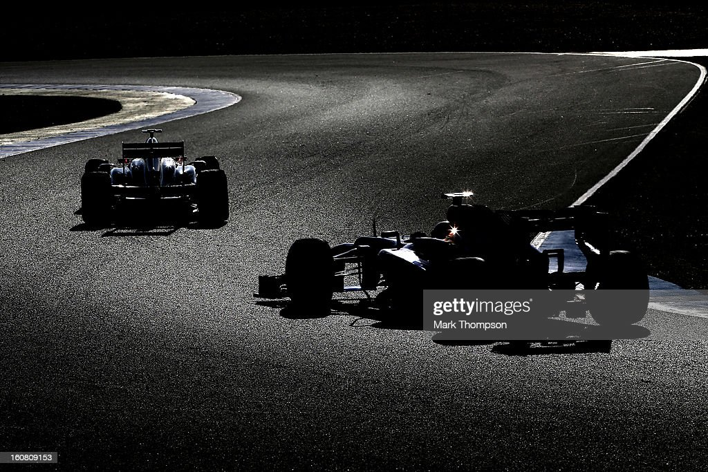 Romain Grosjean of France and Lotus and Mark Webber of Australia and Infiniti Red Bull Racing drive during Formula One winter testing at Circuito de Jerez on February 6, 2013 in Jerez de la Frontera, Spain.