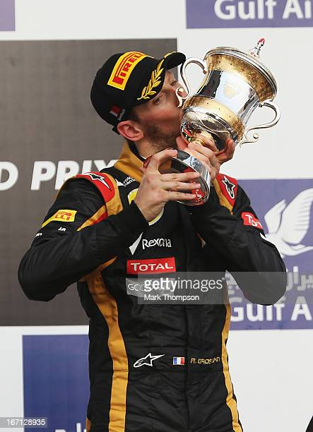 Romain Grosjean of France and Lotus celebrates on the podium after finishing third during the Bahrain Formula One Grand Prix at the Bahrain...