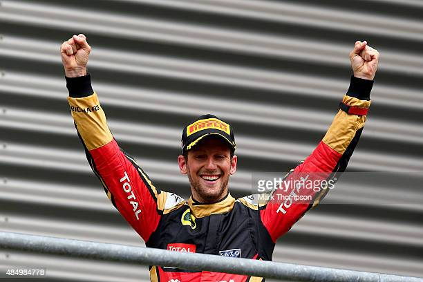 Romain Grosjean of France and Lotus celebrates on the podium after finishing third in the Formula One Grand Prix of Belgium at Circuit de...