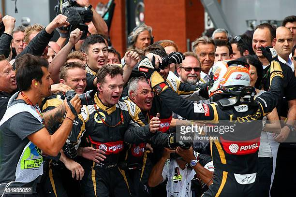 Romain Grosjean of France and Lotus celebrates with his team in Parc Ferme after finishing third in the Formula One Grand Prix of Belgium at Circuit...