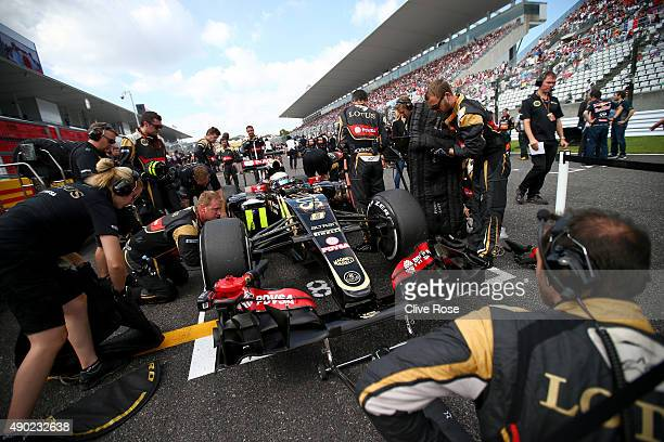 Romain Grosjean of France and Lotus prepares on the grid with his team before the Formula One Grand Prix of Japan at Suzuka Circuit on September 27...