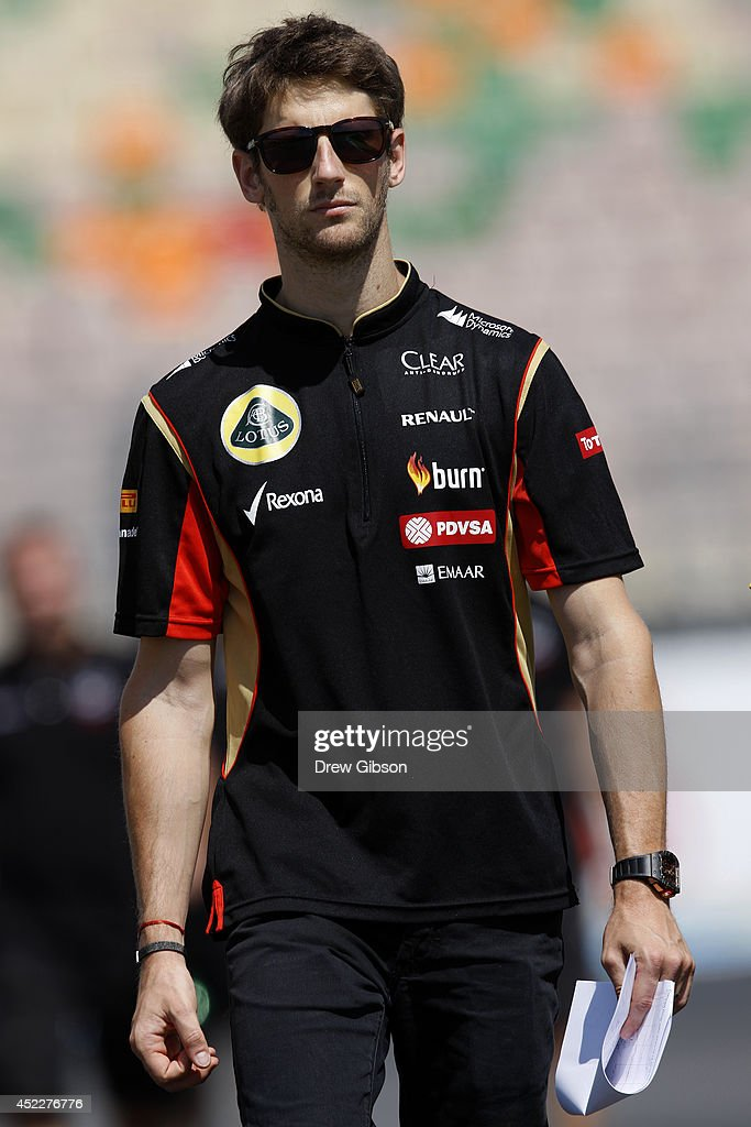 Romain Grosjean of France and Lotus walks along the track with members of his team during previews ahead of the German Grand Prix at Hockenheimring on July 17, 2014 in Hockenheim, Germany.