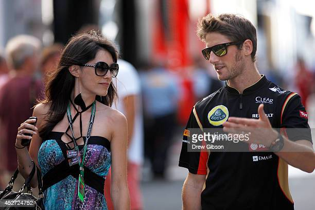 Romain Grosjean of France and Lotus walks through the paddock with his wife Marion Jolles Grosjean after qualifying ahead of the Hungarian Formula...