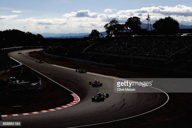 Romain Grosjean of France driving the Haas F1 Team HaasFerrari VF17 Ferrari follows Kimi Raikkonen of Finland driving the Scuderia Ferrari SF70H on...