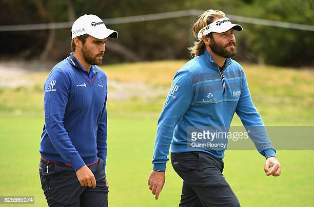 Romain Langasque and Victor Dubuisson of France walk down the fairway during day one of the World Cup of Golf at Kingston Heath Golf Club on November...