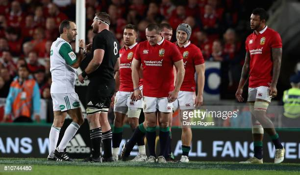 Romain Poite the referee talks to All Black captain Kieran Read after he reverses a decision when he orginally had awarded a penalty to the All...