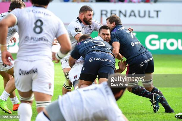 Romain Taofifenua of Toulon is knocked out in a tackle by Paul AloEmile of Stade Francais Paris and Willem Alberts of Stade Francais Paris during the...