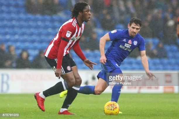 Romaine Sawyers of Brentford is marked by Craig Bryson of Cardiff City during the Sky Bet Championship match between Cardiff City and Brentford at...