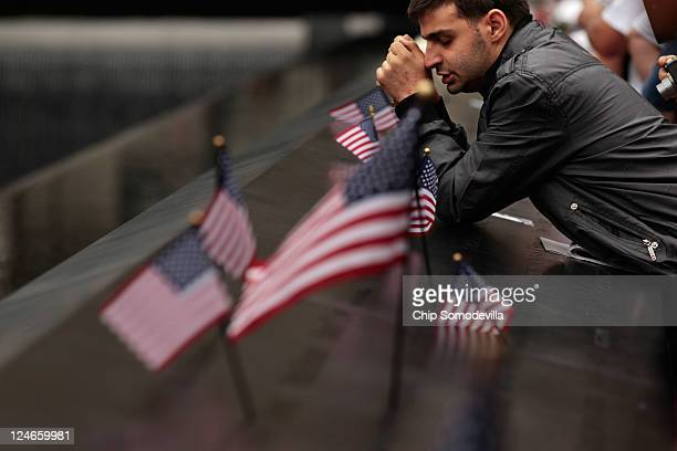 Roman Bondar prays while leaning on the bronze pannels that bear the names of the victims of the September 11 terror attacks at the 9/11 Memorial...