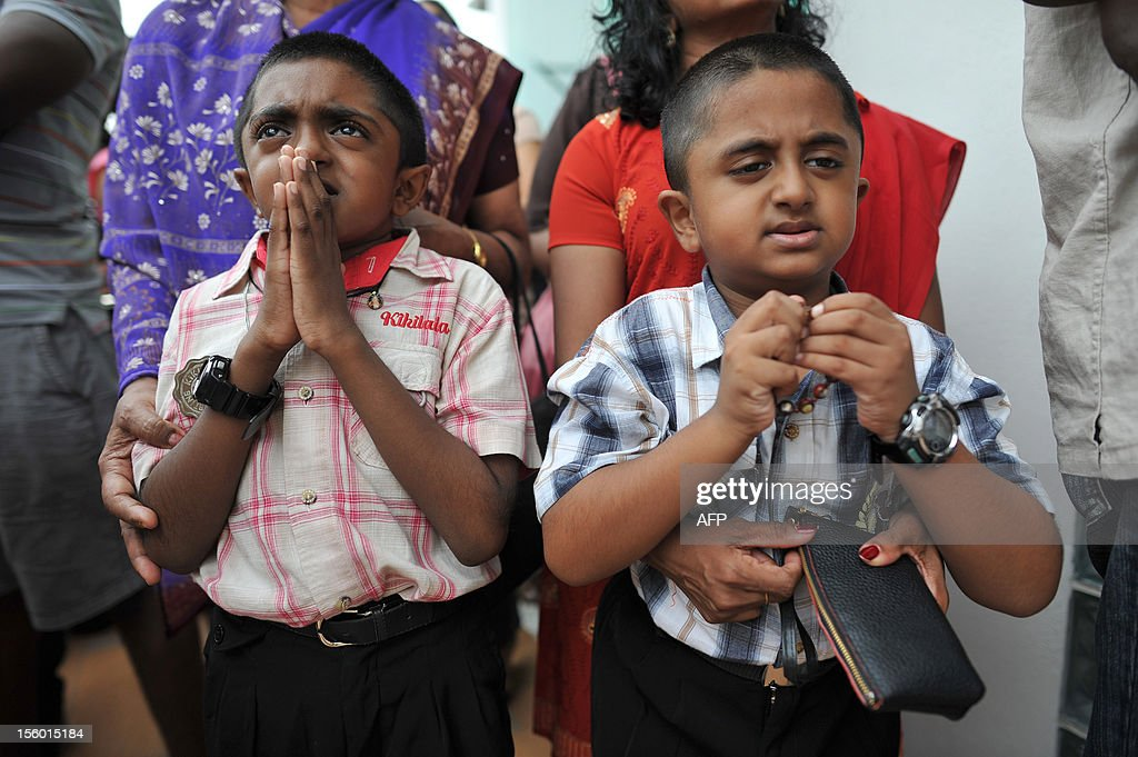 Roman Catholic children offer prayers in front of an image said to be the Virgin Mary (unseen) that appeared on the window of a Malaysian hospital in Subang, outside Kuala Lumpur on November 11, 2012. Pictures of the image have gone viral among local Christians on Facebook this week and large crowds have been seen at the Sime Darby Medical Centre just outside of Kuala Lumpur.