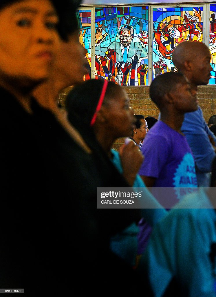 Roman Catholic Christians are pictured in front of a stained glass window depicting former South African President Nelson Mandela at Regina Mundi church in Soweto on March 31, 2013. Mandela is spending his fourth day in hospital after making 'steady progress' for a recurring lung infection. The 94 year old is idolised in his home nation. It is the second time within a month that he has been admitted to hospital, after spending a night for check-ups on March 9, 2013. AFP PHOTO/Carl de Souza