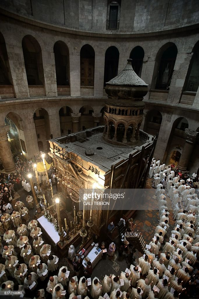 Roman Catholic clergymen hold candles as they circle the Aedicula during the Holy Thursday mass at the Church of the Holy Sepulchre in Jerusalem's...