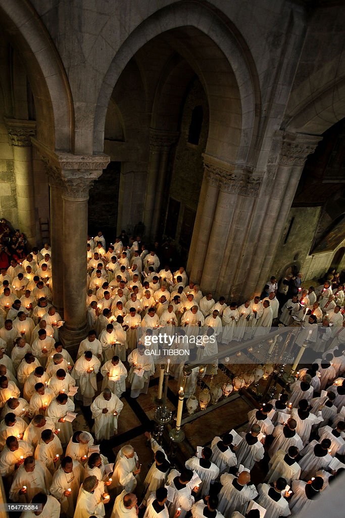 Roman Catholic clergymen hold candles as they circle the Anointing Stone during the Holy Thursday mass at the Church of the Holy Sepulchre in Jerusalem's old city on March 28, 2013 ahead of Easter celebrations. Christians around the world are marking the Holy Week, commemorating the crucifixion of Jesus Christ, leading up to his resurrection on Easter. Christians traditionally believe the church is built on the site where Jesus was crucified and buried.