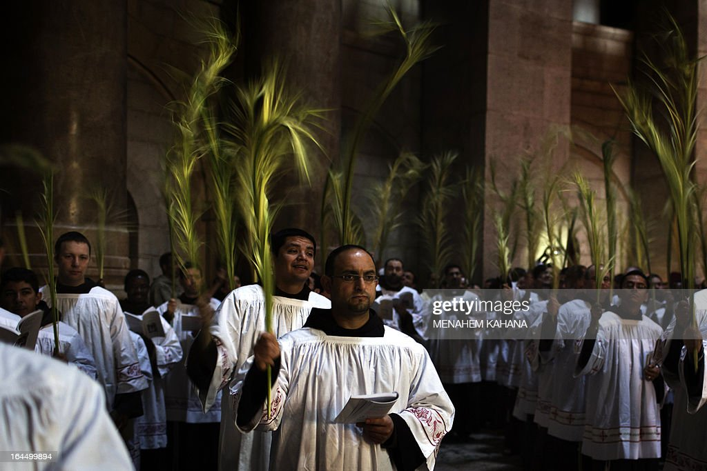 Roman Catholic clergymen hold palm branches as they circle the aedicule during the Palm Sunday procession at the Church of the Holy Sepulcher in Jerusalem's old city on March 24, 2013. Palm Sunday marks the triumphant return of Jesus Christ to Jerusalem when a cheering crowd greeted him waving palm leaves, a week before his crucifixion. AFP PHOTO/MENAHEM KAHANA
