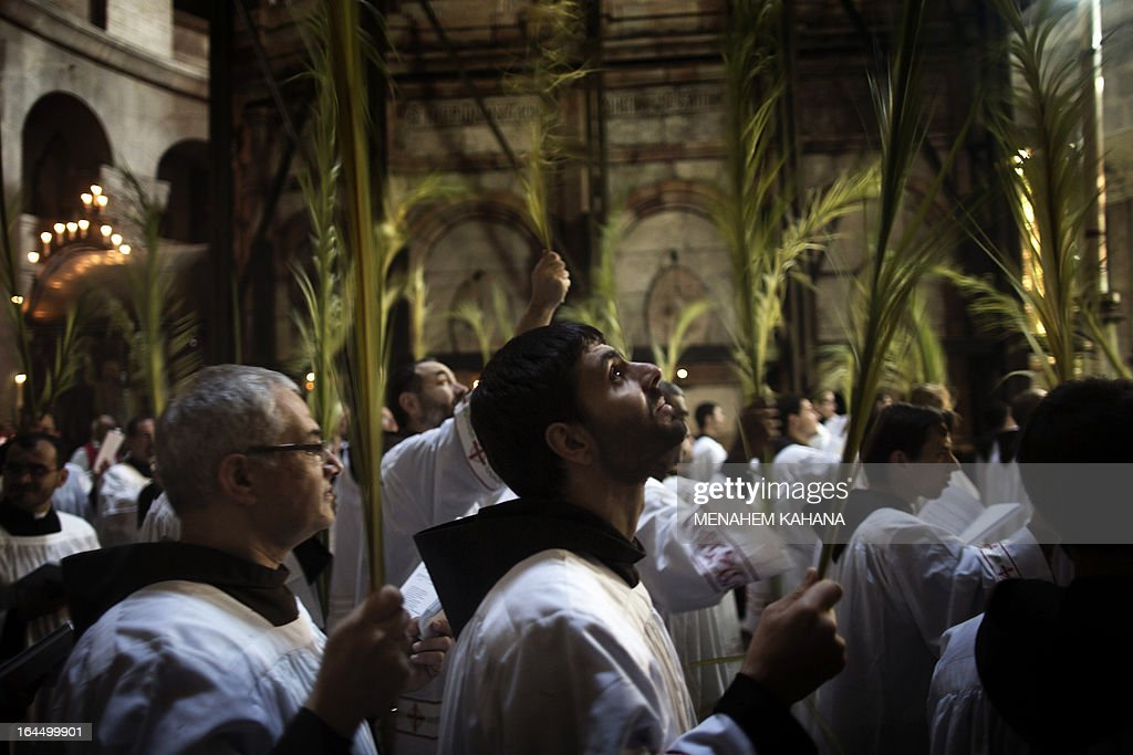 Roman Catholic clergymen hold palm branches as they circle the aedicule during the Palm Sunday procession at the Church of the Holy Sepulcher in Jerusalem's old city on March 24, 2013. Palm Sunday marks the triumphant return of Jesus Christ to Jerusalem when a cheering crowd greeted him waving palm leaves, a week before his crucifixion.