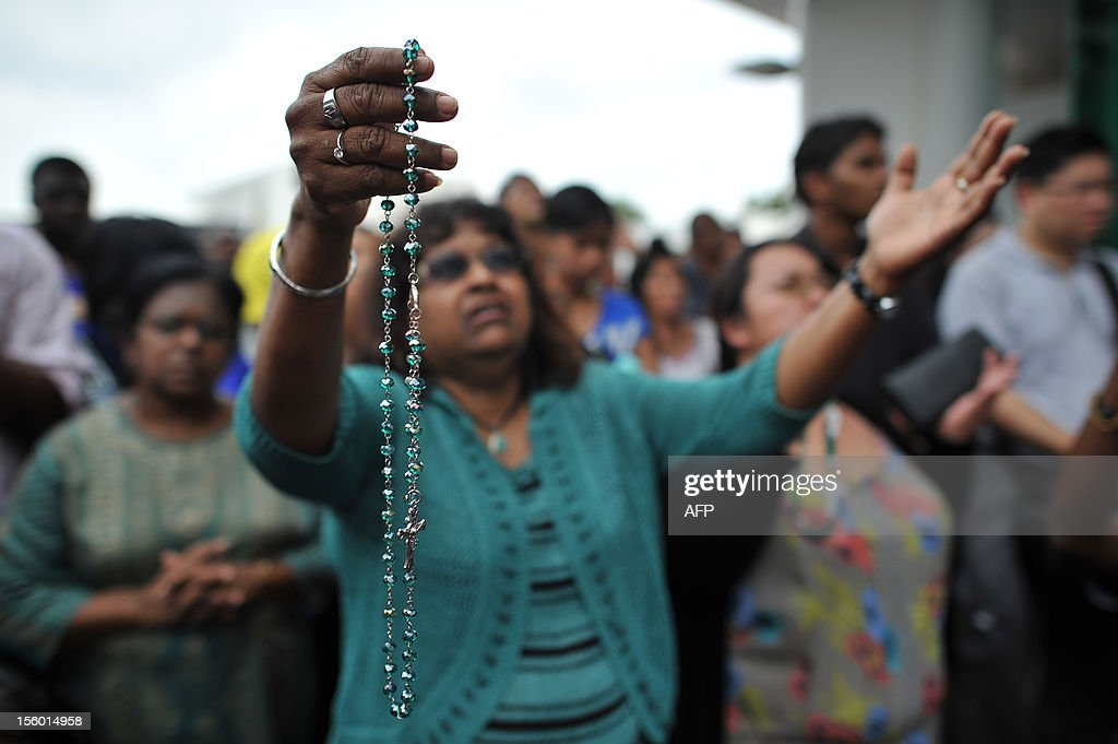 A Roman Catholic devotee offers a prayer in front of an image said to be the Virgin Mary (unseen) that appeared on the window of a Malaysian hospital in Subang, outside Kuala Lumpur on November 11, 2012. Pictures of the image have gone viral among local Christians on Facebook this week and large crowds have been seen at the Sime Darby Medical Centre just outside of Kuala Lumpur.