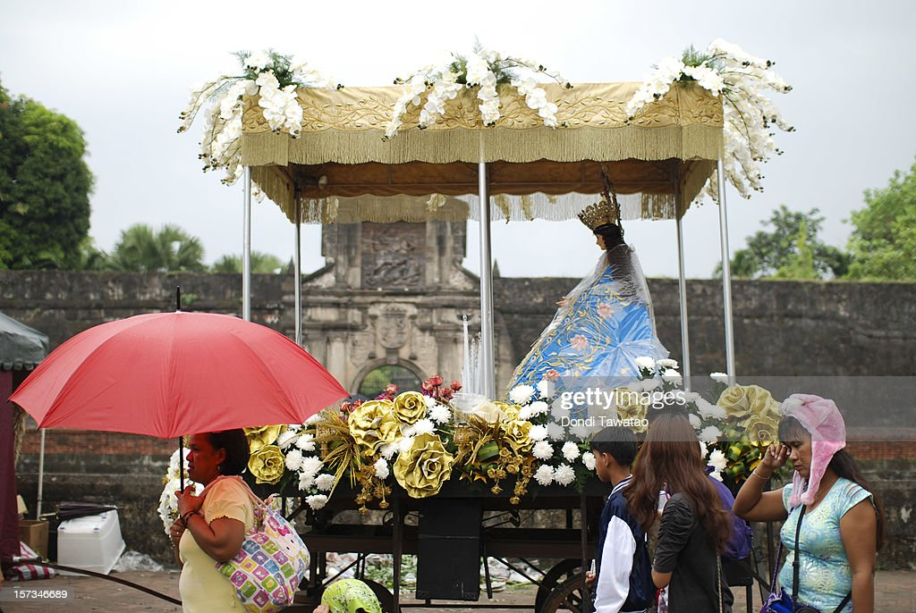 Roman Catholic devotees march in a procession during the Grand Marian Procession celebrating the immaculate conception of the Virgin Mary in Intramuros on December 2, 2012 in Manila, Philippines. Devout Catholics gather in Intramuros to view the ninety statues of the Virgin Mary from different parts of the Philippines being carried through the streets of the walled city of Intramuros. The annual event attracts thousands of devotees and is a mix of rich Catholic tradition along with Filipinos' penchant for year-round festivities.