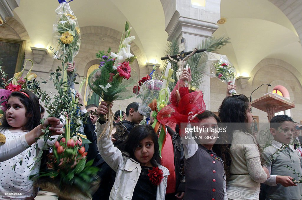 Roman Catholic kids hold branches and flowers during a mass marking the Palm Sunday at the Church of Santa Cathrina in the Church of the Nativity Compound in the West Bank city of Bethlehem on March 24, 2013. Palm Sunday marks the triumphant return of Jesus Christ to Jerusalem when a cheering crowd greeted him waving palm leaves, a week before his crucifixion. AFP PHOTO/MUSA AL-SHAER