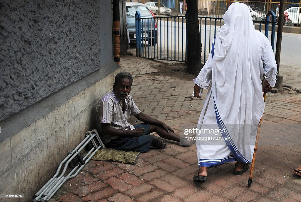 A Roman Catholic nun of the Missionaries of Charity order walks past a leprosy patient as she leaves a service to commemorate the 17th death...