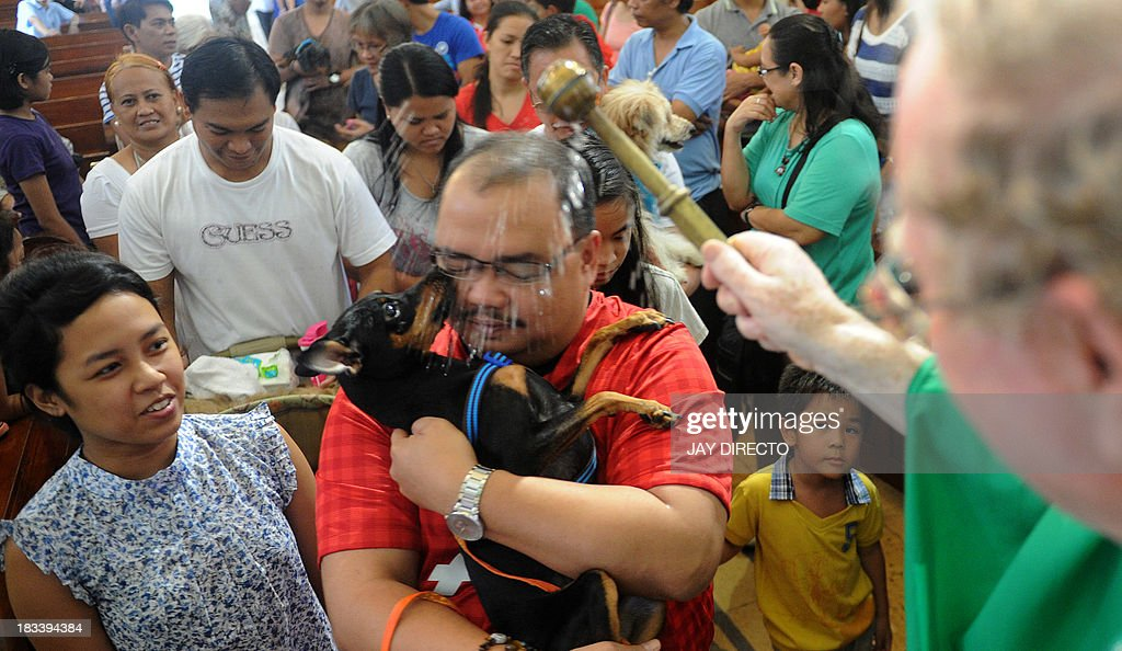 A Roman Catholic priest blesses animals with holy water on the first Sunday of October after a mass for World Animal Day in Manila on October 6, 2013. People around the globe celebrated World Animal Day, which began as a holiday in Florence, Italy, in 1931 at a convention of ecologists, to highlight the plight of endangered species. AFP PHOTO / Jay DIRECTO