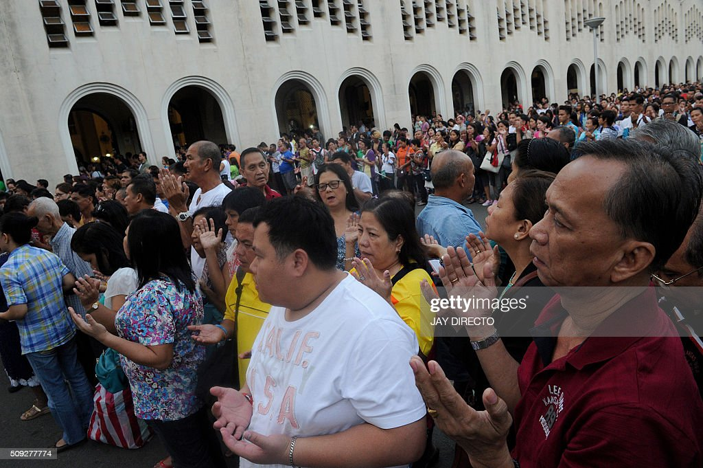 Roman Catholics devotees pray out side the church as the country marks Ash Wednesday, the official beginning of the Christian Lenten season in Manila on February 10, 2016. The Philippines is Asia's bastion of Catholicism, with over 80 percent of the more than 100 million population belonging to the faith. AFP PHOTO / Jay DIRECTO / AFP / JAY DIRECTO