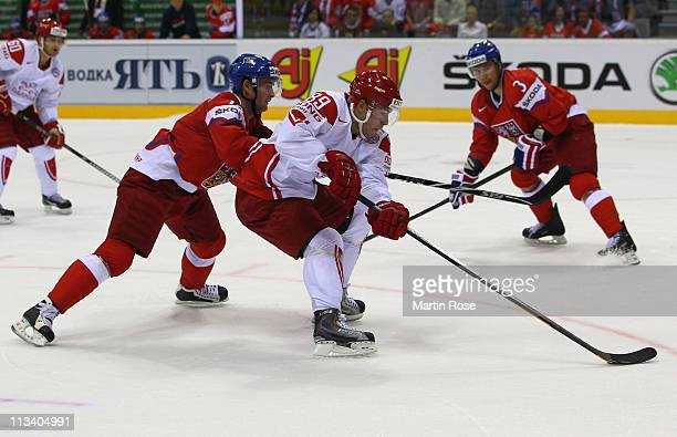 Roman Cervenka of Czech Republic and Mikkel Bodker of Denmark battle for the puck during the IIHF World Championship group D match between Czech...