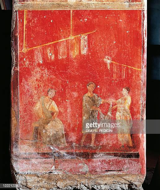 Roman civilization 1st century AD Pompeii Fullonica of Veranio Ipseo Pilaster of the fullers depicting woolworking A maidservant gives a woman...