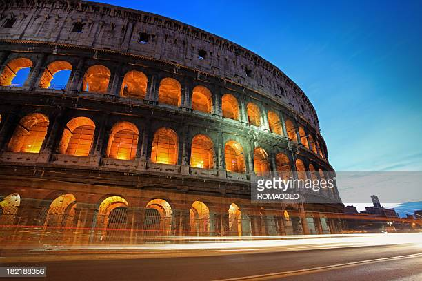 Roman coliseum at night with lights and traffic whizzing by