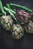 Roman artichokes with texture on a dark background. Ingredients of southern Italian cuisine. Vertical format