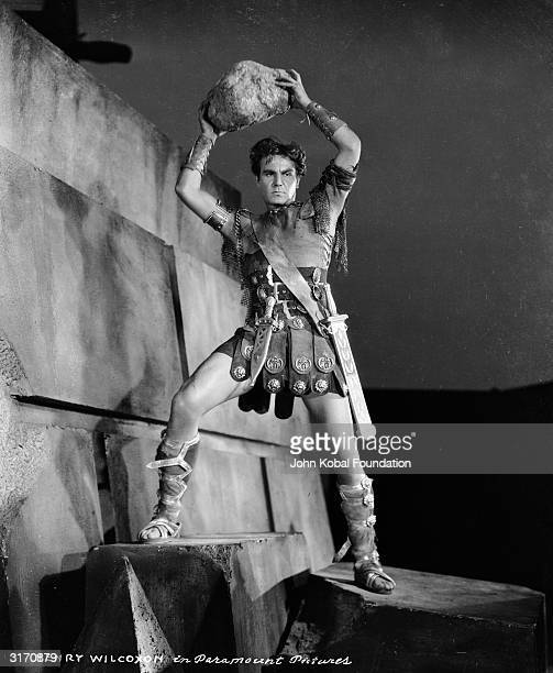 Roman general Marc Antony played by Henry Wilcoxon lifts a rock high above his head in the historical drama 'Cleopatra' directed by Cecil B DeMille