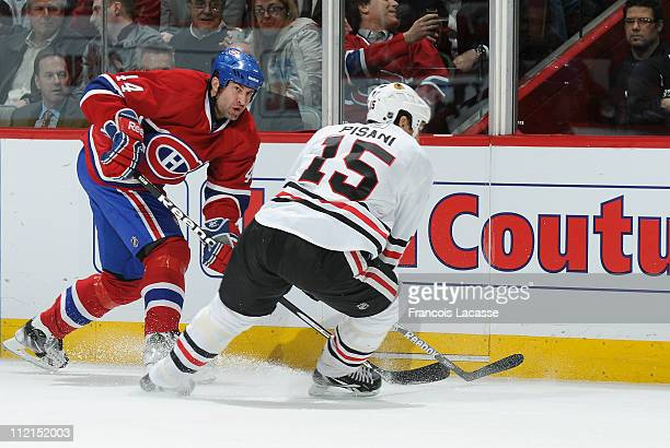 Roman Hamrlik of the Montreal Canadiens battles for the puck with Fernando Pisani of the Chicago Blackhawks during the NHL game on April 5 2011 at...