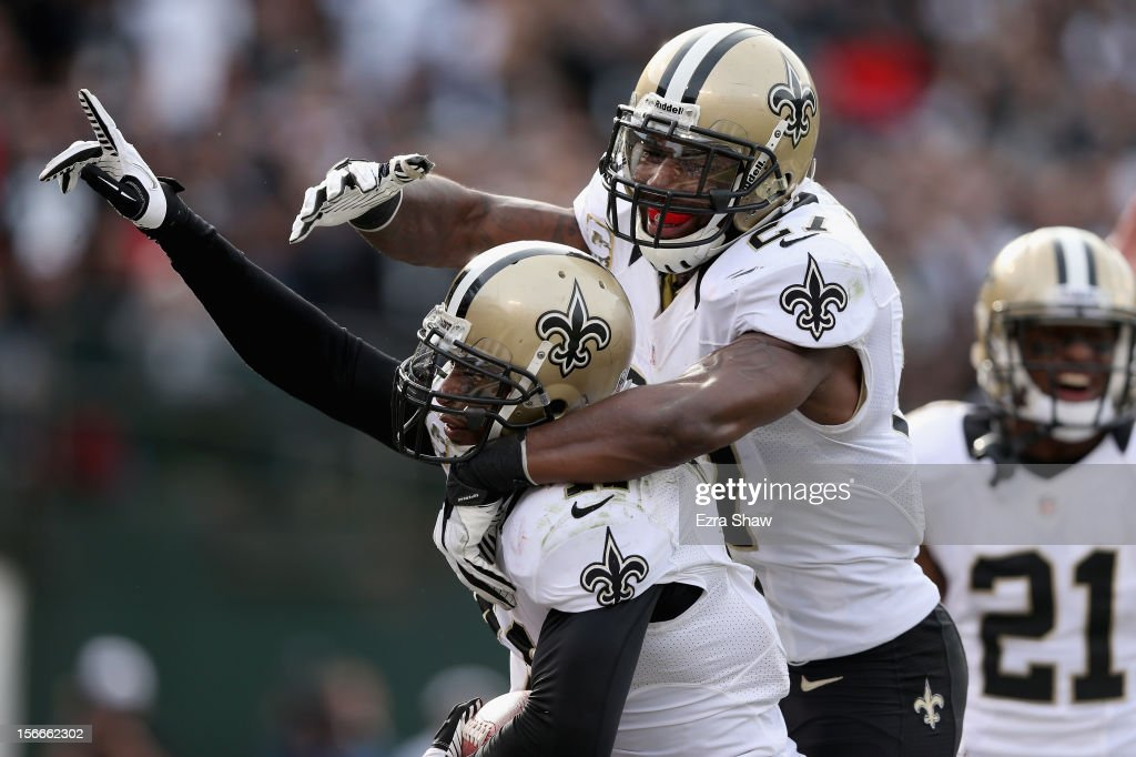 Roman Harper of the New Orleans Saints is congratulated by Malcolm Jenkins after Harper intercepted the ball in the endzone during their game against...