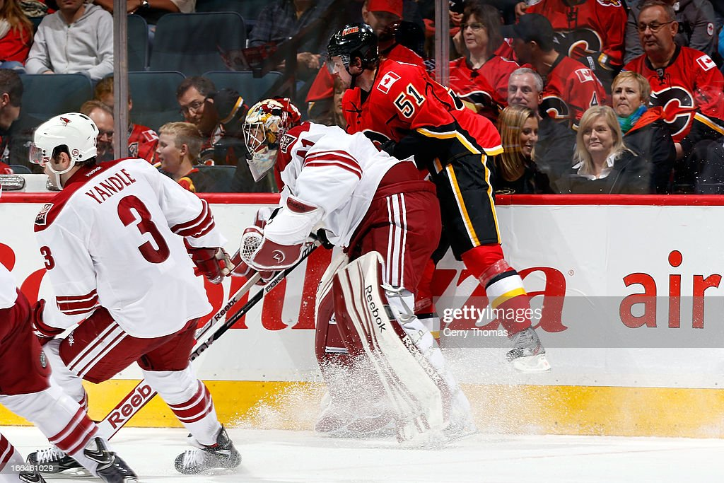 Roman Horak #51 of the Calgary Flames is checked by Mike Smith #41 of the Phoenix Coyotes on April 12, 2013 at the Scotiabank Saddledome in Calgary, Alberta, Canada.