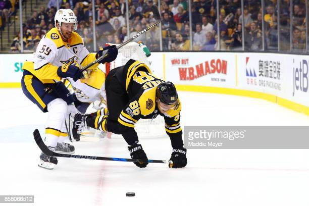 Roman Josi of the Nashville Predators checks David Pastrnak of the Boston Bruins during the third period at TD Garden on October 5 2017 in Boston...