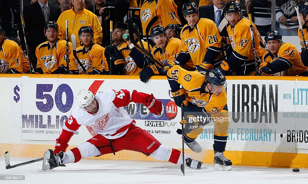 <a gi-track='captionPersonalityLinkClicked' href=/galleries/search?phrase=Roman+Josi&family=editorial&specificpeople=4247871 ng-click='$event.stopPropagation()'>Roman Josi</a> #59 of the Nashville Predators collects a loose puck and scores an empty net goal against <a gi-track='captionPersonalityLinkClicked' href=/galleries/search?phrase=Darren+Helm&family=editorial&specificpeople=3949334 ng-click='$event.stopPropagation()'>Darren Helm</a> #43 of the Detroit Red Wings at Bridgestone Arena on December 30, 2013 in Nashville, Tennessee.