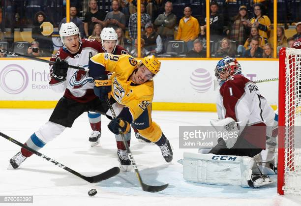 Roman Josi of the Nashville Predators drives to the net against Nathan MacKinnon and Semyon Varlamov of the Colorado Avalanche during an NHL game at...