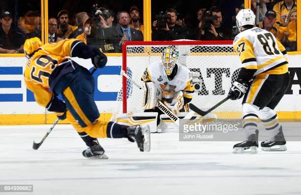 Roman Josi of the Nashville Predators fires a shot towards Matt Murray of the Pittsburgh Penguins as Sidney Crosby of the Pittsburgh Penguins looks...