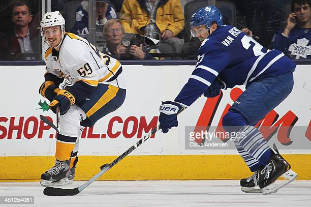 Roman Josi of the Nashville Predators flips the puck past James van Riemsdyk of the Toronto Maple Leafs during an NHL game at the Air Canada Centre...