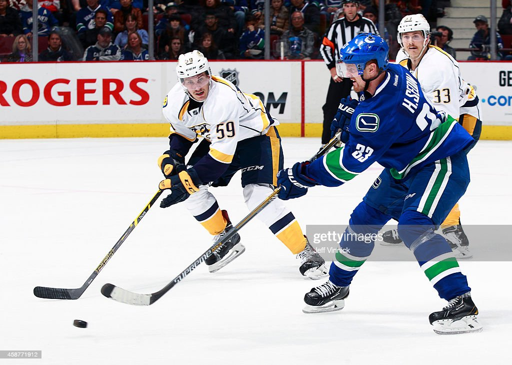 <a gi-track='captionPersonalityLinkClicked' href=/galleries/search?phrase=Roman+Josi&family=editorial&specificpeople=4247871 ng-click='$event.stopPropagation()'>Roman Josi</a> #59 of the Nashville Predators looks on as <a gi-track='captionPersonalityLinkClicked' href=/galleries/search?phrase=Henrik+Sedin&family=editorial&specificpeople=202574 ng-click='$event.stopPropagation()'>Henrik Sedin</a> #33 of the Vancouver Canucks passes the puck up ice during their NHL game at Rogers Arena November 2, 2014 in Vancouver, British Columbia, Canada.