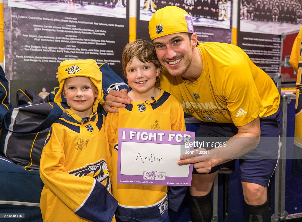 Roman Josi #59 of the Nashville Predators poses with cancer survivor Andie Owens and her sister Stacy after a 6-3 win against the Washington Capitals on Hockey Fights Cancer Night at Bridgestone Arena on November 14, 2017 in Nashville, Tennessee.