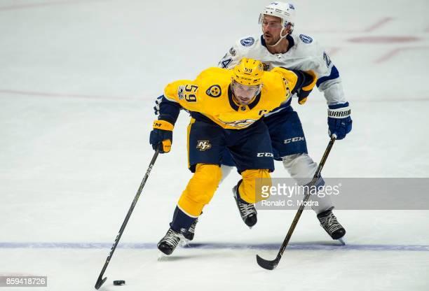 Roman Josi of the Nashville Predators skates with the puck as Ryan Callahan of the Tampa Bay Rays chases during a NHL preseason game at Bridgestone...